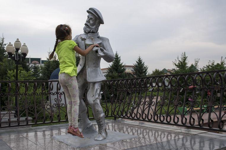 Een meisje speelt met het standbeeld van een vioolspeler van kunstenaar Vladislav Tsak. Beeld Yuri Kozyrev