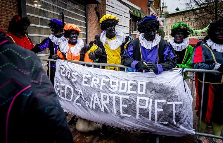 Actievoerders voor het behoud van Zwarte Piet met een spandoek