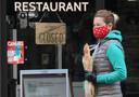 Een vrouw met mondkapje loopt langs een gesloten restaurant in Parijs.