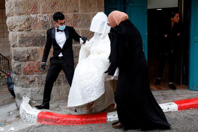 Imad Sharaf en Bara'a Amarneh laten zich door het coronavirus niet weerhouden van hun bruiloft.  Met mondkapjes op en handschoenen aan lopen ze in het Palestijnse vluchtelingenkamp Deheisheh, nabij Bethlehem, naar hun trouwplechtigheid.