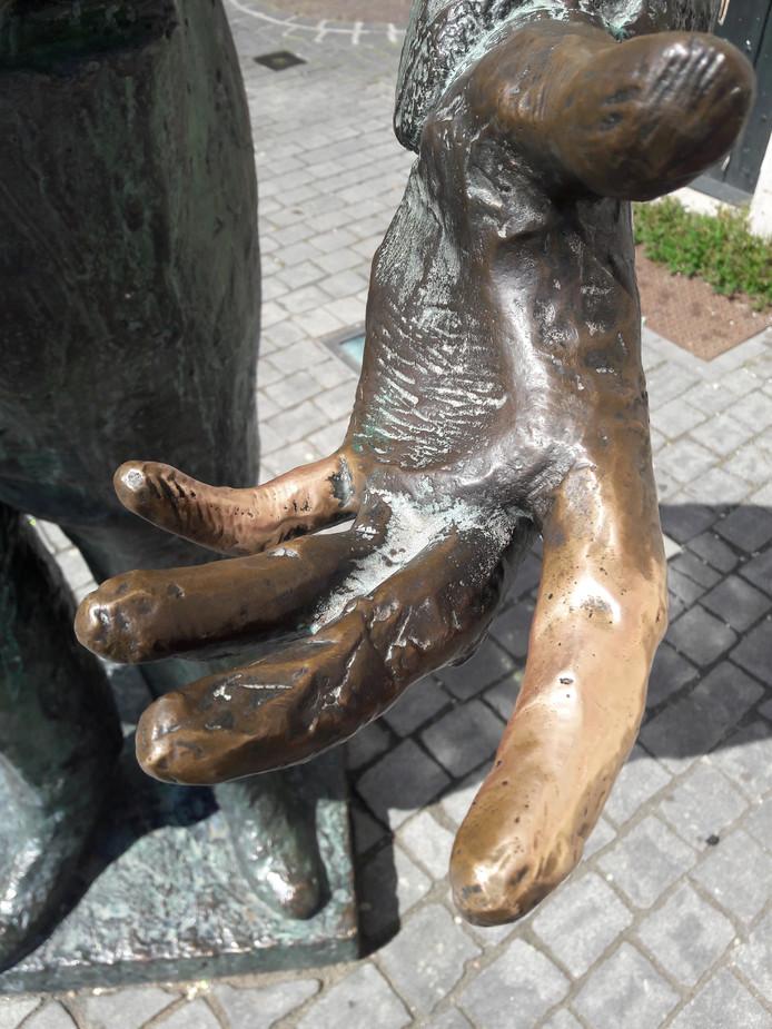 De vingers van het bronzen standbeeld van Anton van Duinkerken verraden op de Grote Markt van Bergen op Zoom intensief gebruik