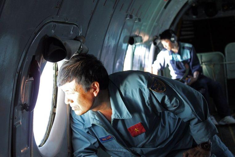 Een bemanningslid van een toestel van de Vietnamese luchtmacht kijkt uit naar sporen van de verdwenen Boeing van Malaysia. Beeld afp