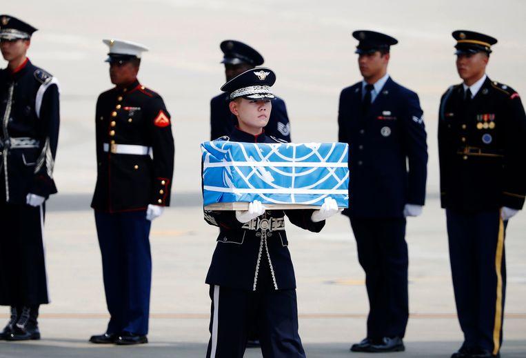 Tijdens een ceremonie op de Zuid-Koreaanse luchtmachtbasis Osan, werden de oorlogsresten van 55 Amerikaanse soldaten uit een transportvliegtuig gehaald.  Beeld AP