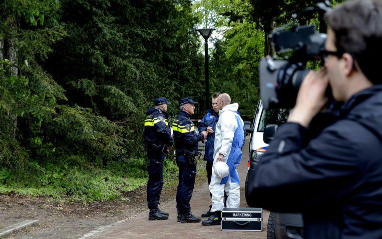 Overleg tussen agenten en medewerkers van een forensisch team op de plek waar twee mensen door blikseminslag zijn overleden. Beeld anp
