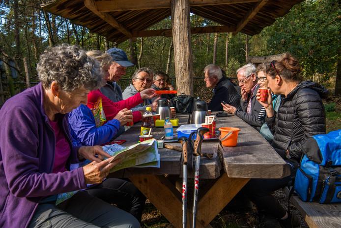 De wandelgroep rust even uit aan een picknicktafel bij Bosschuur de Meren in Wintelre.