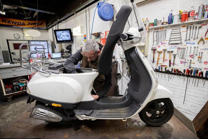 Mark Dijkmans heeft zijn handen vol aan het repareren van scooters die kapot gingen doordat er verkeerde brandstof getankt is. Foto: Kees Maartens/Fotomeulenhof