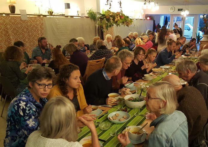 Aan lange tafels wordt maandelijks de maaltijd in het Soepcafé in Olst genuttigd.