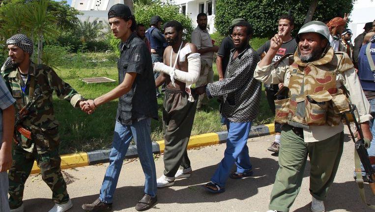 Strijders van het nieuwe bewind in Libië begeleiden gevangenen in Sirte. Beeld reuters