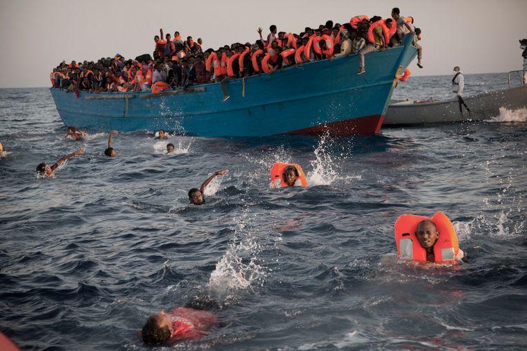 Vluchtelingen springen van een houten bootje om gered te worden door een ngo voor de kust van Libië.