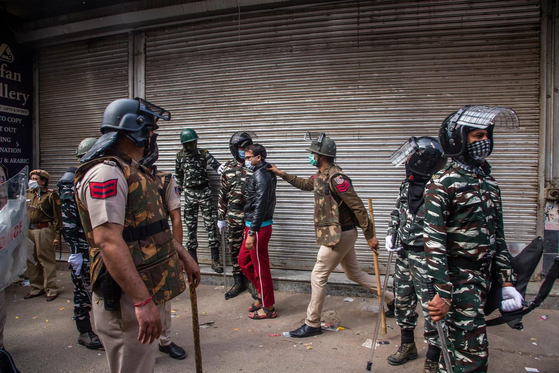 Een politieman neemt een moslim mee na protesten in Delhi.