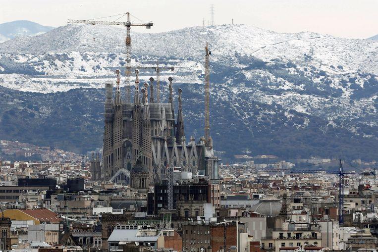 Tegen de achtergrond van de besneeuwde heuvels van Collserola pronkt de Sagrada Família in hartje Barcelona.  Beeld EPA