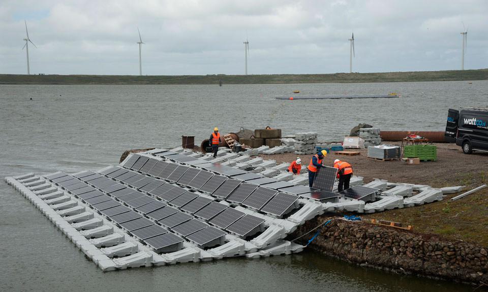 Zowel langs de kant als midden op het water van de Slufter worden drijvende zonnepanelen geplaatst.