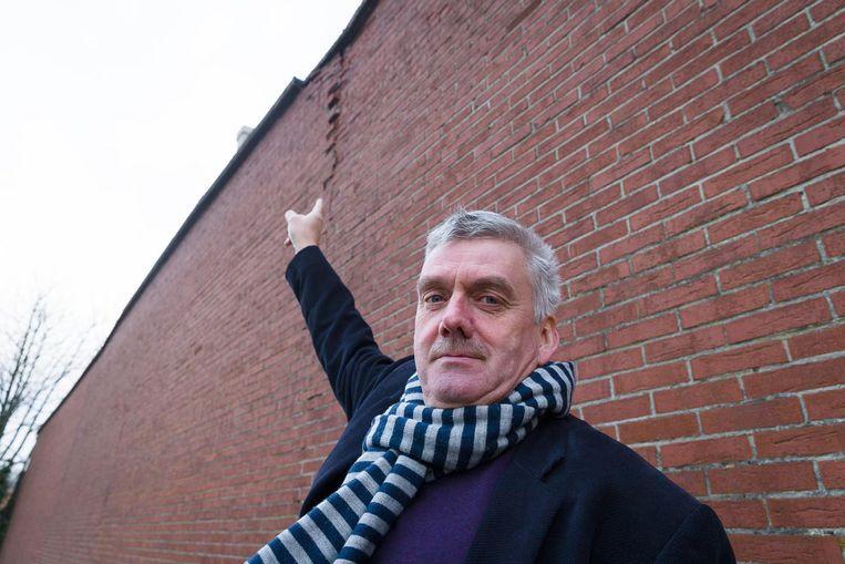 Burgemeester Frank Bruggeman toont de muur die dreigde om te waaien.