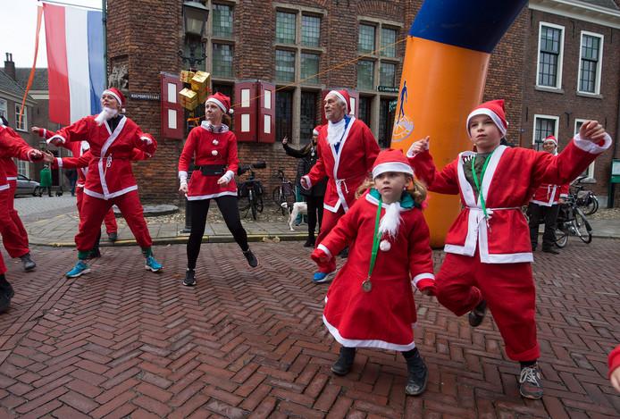 Hardlopers in kerstpak bij de Santarun doen een warming up.