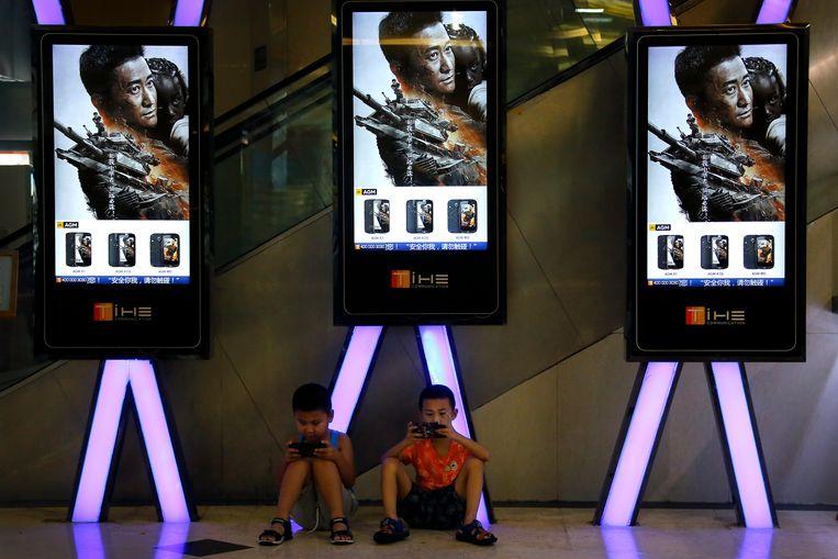 Kinderen spelen met hun telefoon onder reclames voor de patriottische superheldenfilm 'Wolf Warrior 2', de kaskraker van afgelopen zomer. Beeld AP