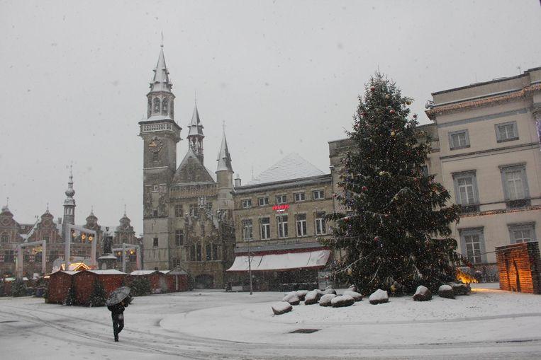 De kerstboom en chalets op de Grote Markt zijn bedekt met een laagje sneeuw.