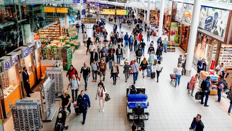 Reizigers in de vertrekhal van luchthaven Schiphol. Beeld anp