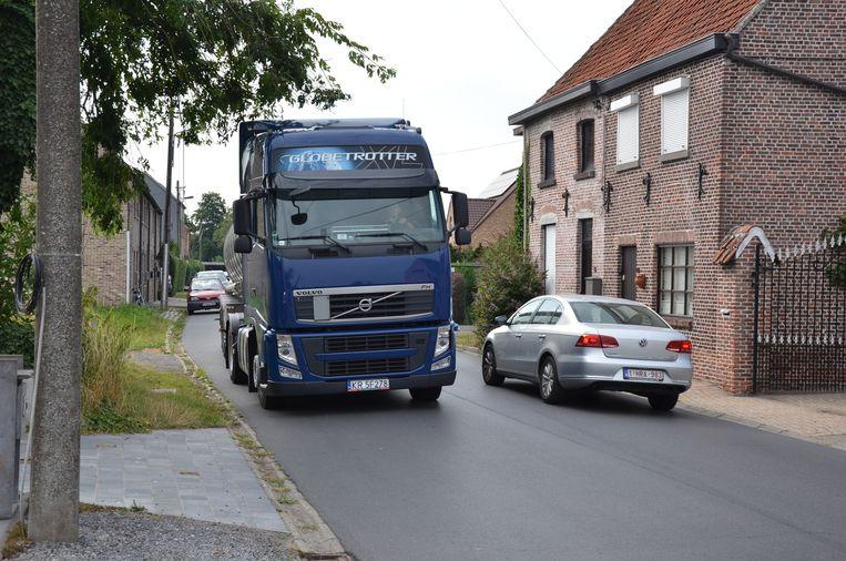 Een vrachtwagen laveert door de Sint-Elooistraat. Vooral 's ochtends vroeg en 's avonds rijden ze door de buurt.