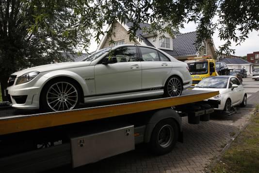 Een auto wordt in beslag genomen door de politie en de FIOD bij een inval op een woonwagenkamp in Breda