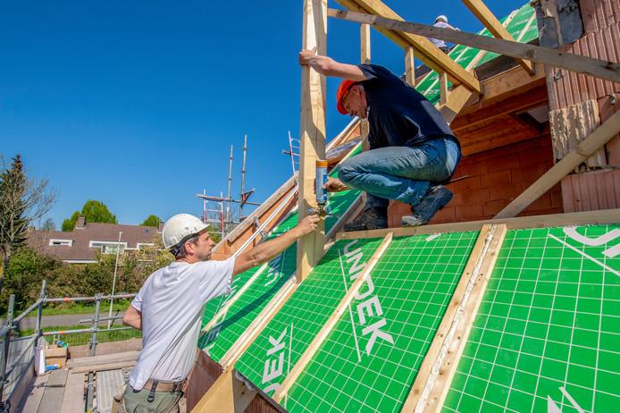 Aan de Bulkstraat in Wouw worden woningen gebouwd. Bouwvakkers zijn bezig met het leggen van de dakpanelen.