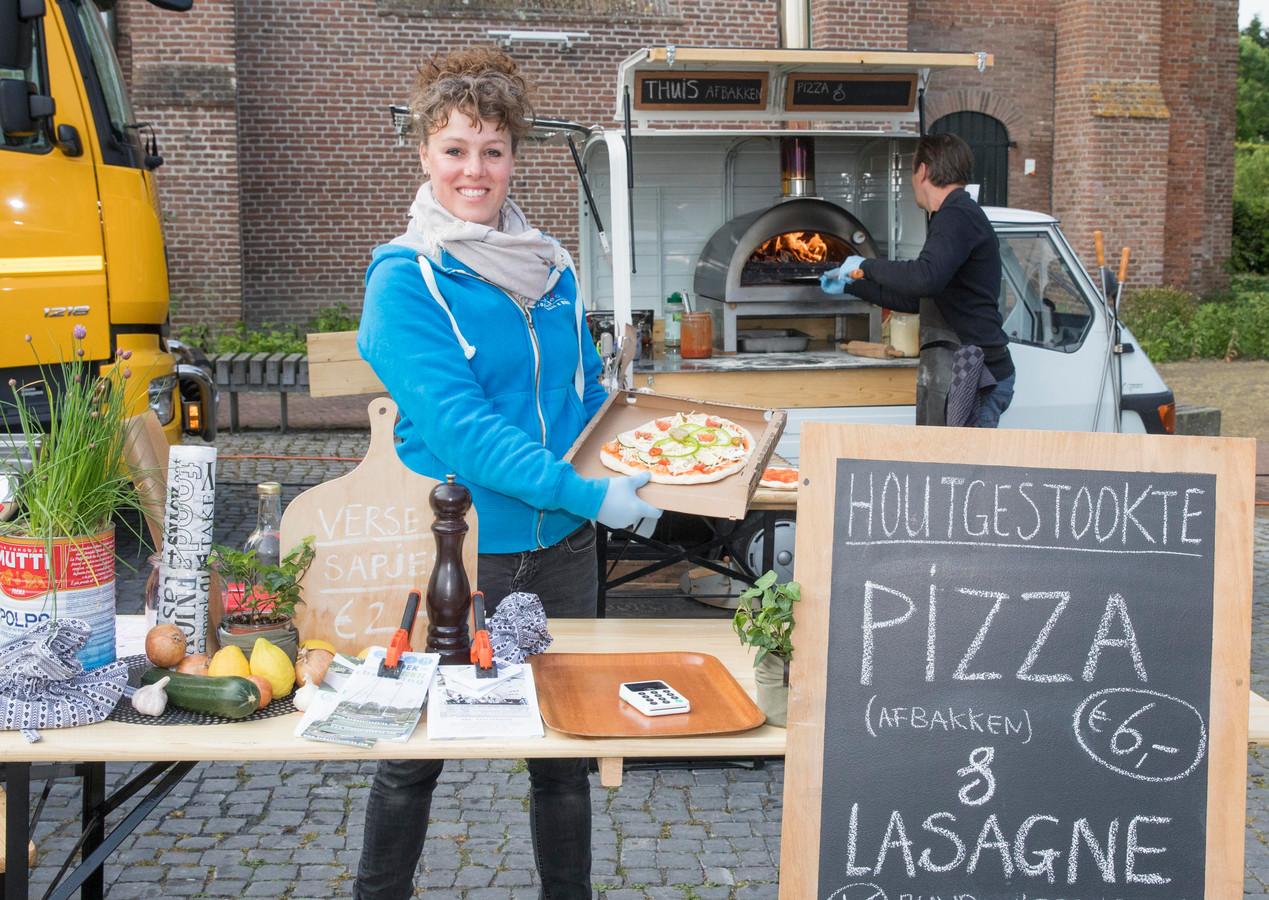 Ivonne Bom met op de achtergrond Peter van der Geest achter de houtgestookte oven.