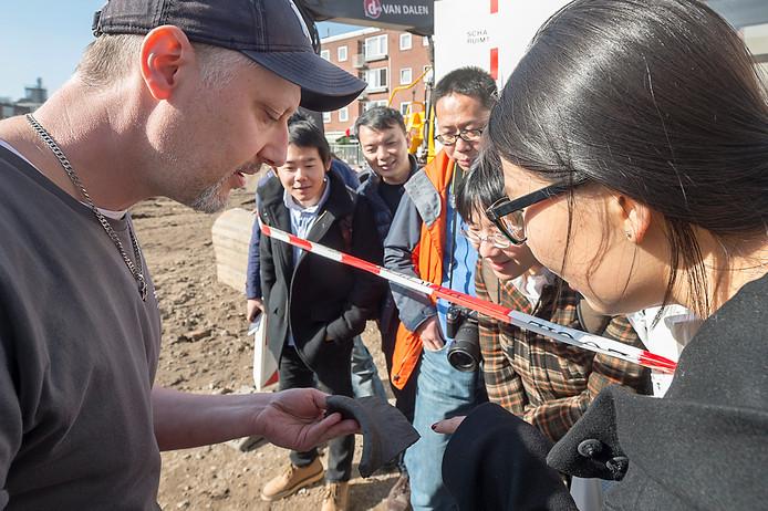 Archeoloog Leo Smole toont de delegatie de laatste vondst van de opgravingen op het Kerkplein: een schede van een zwaard uit de middeleeuwen.