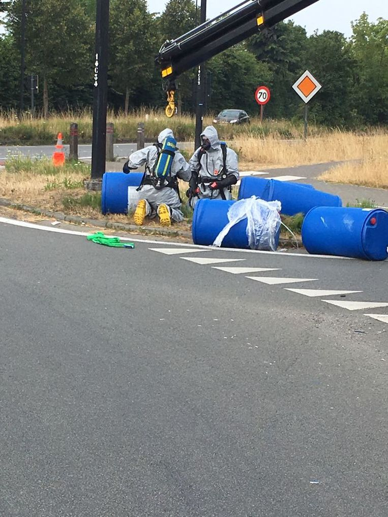 Met speciale pakken en gasmaskers werden de tonnen één voor één van de weg gehaald.