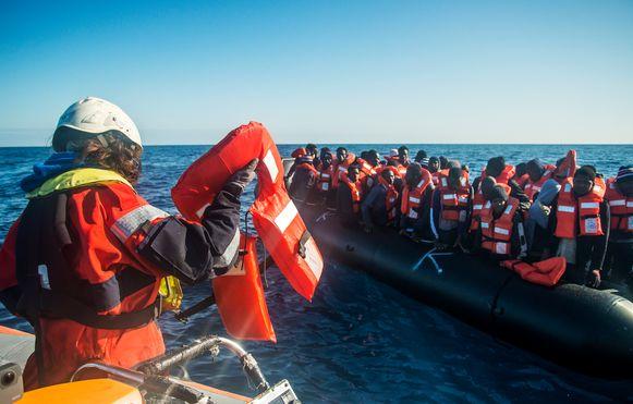 Medewerkers van Seawatch helpen migranten aan boord van het schip