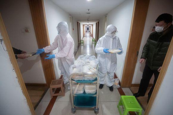 Medisch personeel deelt maaltijden uit aan mensen die in quarantaine zitten in door de staat gerunde hotels.