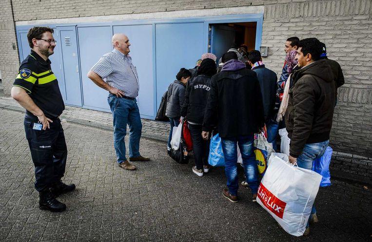 Vluchtelingen komen aan bij een registratielocatie in Rotterdam-IJsselmonde. Beeld anp