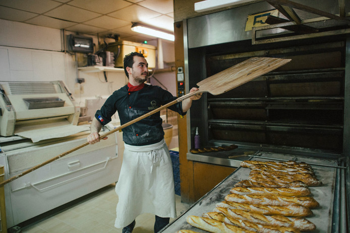 Een bakker haalt verse baguettes uit de oven.
