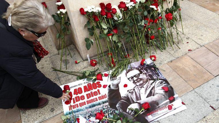 Een Chileense vrouw legt een roos op een afbeelding van president Salvador Allende, die 40 jaar geleden werd verdreven door een staatsgreep onder leiding van generaal Augusto Pinochet. Beeld epa
