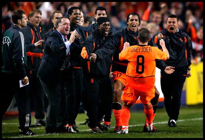 Bondscoach Dick Advocaat en de reservespelers zien Wesley Sneijder op zich af komen na zijn 1-0 tegen Schotland.