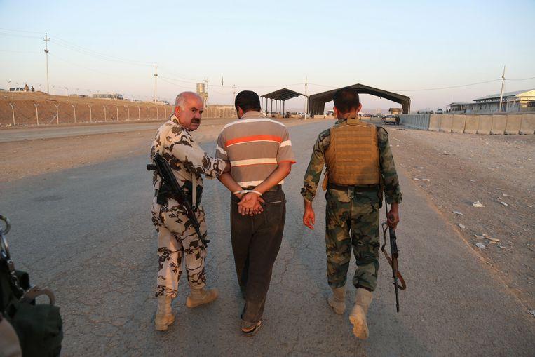 Koerdische strijders nemen een man gevangen van wie zij vermoeden dat hij voor IS vecht. Locatie: Khazer checkpoint, net buiten Erbil. Beeld null