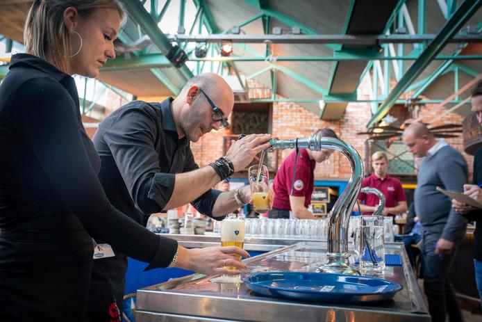 Roderick Maijer vult het glas tijdens de biertapwedstrijd in de Foodhall Arnhem. Links van hem Eva Vulperhorst, met wie hij een koppel vormde tijdens de wedstrijd voor duo's.
