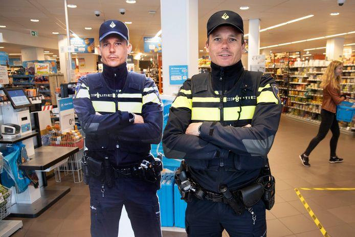 De Nijmeegse wijkagent Koen Meeuwsen naast zijn alter ego die het zelfscanplein bij de Albert Heijn op de Daalseweg bewaakt.