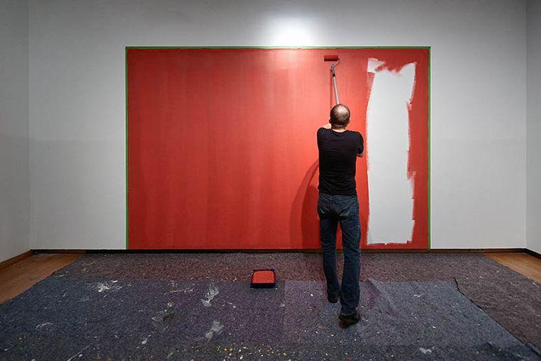 Steven Aalders schildert een muur in het Van Gogh Museum in een steenrode kleur, als onderdeel van zijn kunstwerk   Beeld Jan-Kees Steenman