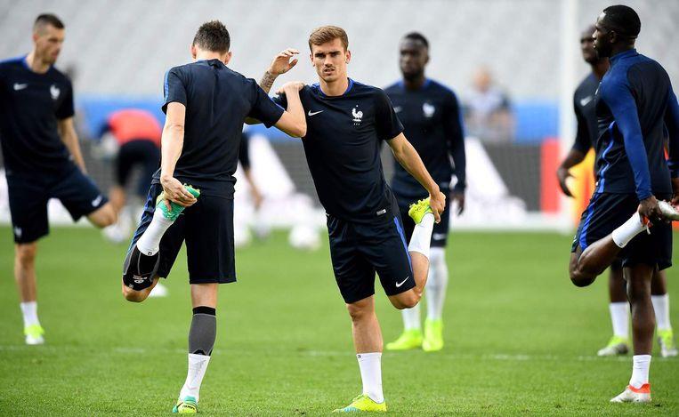 Fransman Antoine Griezmann rekt zijn bovenbeen tijdens een training ter voorbereiding op de openingswedstrijd. Beeld null