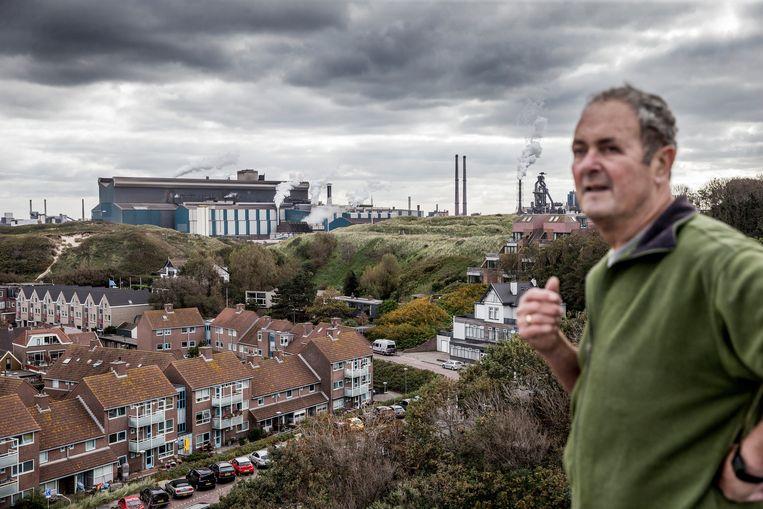 Paul Meiland, bewoner van Wijk aan Zee, laat zien hoe dicht Tata Steel bij Wijk aan Zee ligt. Beeld Jean-Pierre Jans