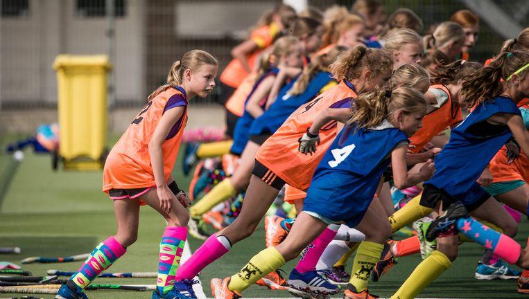 Meisjes van hockeyclub Terriërs in Heiloo nemen deel aan een sprintoefening tijdens de selectietraining. Beeld Freek van den Bergh/de Volkskrant