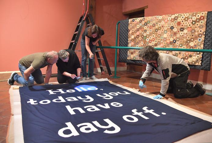 Het geborduurde spandoek van de Britse kunstenaar Jeremy Deller wordt gereedgemaakt om op te hangen.