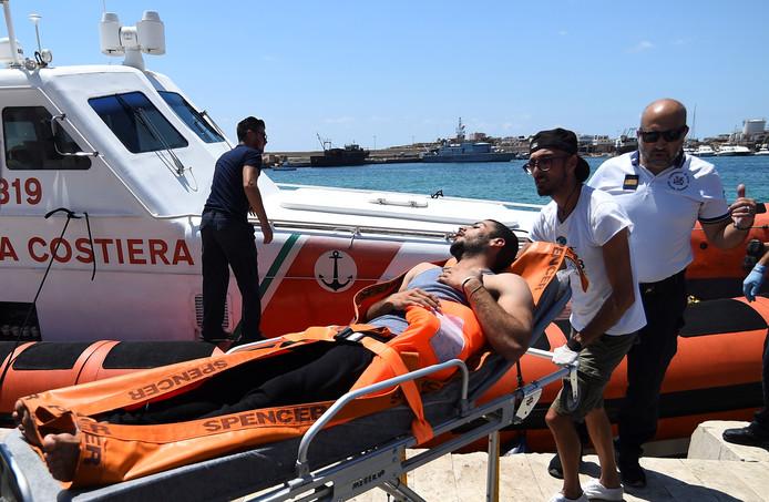 Een aan land gebrachte migrant wordt door hulpverleners afgevoerd.