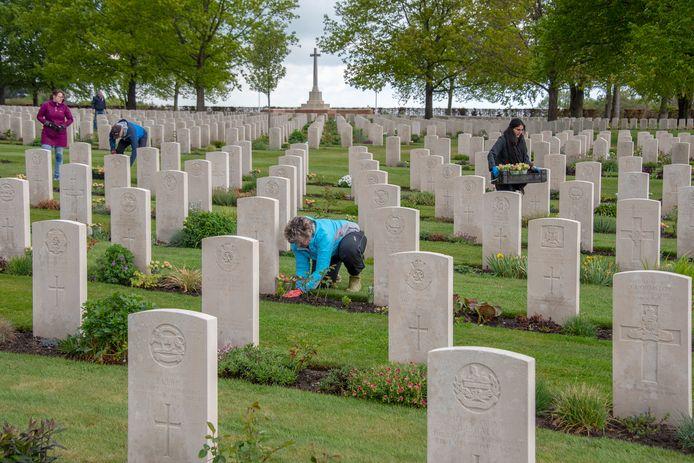 Vrijwilligers van de stichting Faces to Graves zetten de vaasjes met tulpen bij de graven op de Canadese begraafplaats.