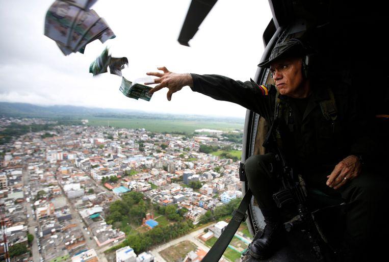 Het team van de anti-narcoticapolitie gooit flyers uit een helicopter waarin wordt opgereoepen om informatie (anoniem) te delen over cocalaboratoria en leden van illegale drugsbendes die politieagenten hebben vermoord in Colombia.