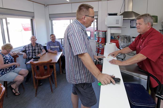 PVH Oijen Wim van Rooij (rechts) neemt bestelling op in zijn snackbar Wimke.