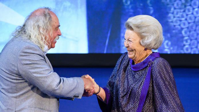 Prinses Beatrix reikt een Zilveren Anjer uit aan Paul Spapens .