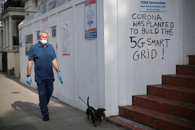 Een man met mondkapje loopt langs een protestleus tegen 5G in Londen, Groot-Brittannië. REUTERS/Hannah McKay Beeld REUTERS