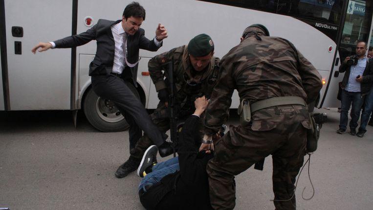 Een betoger wordt geschopt door Yusuf Yerkel, adviseur van Erdogan, terwijl agenten hem vasthouden tijdens een protest tegen het bezoek van Erdogan aan Soma.