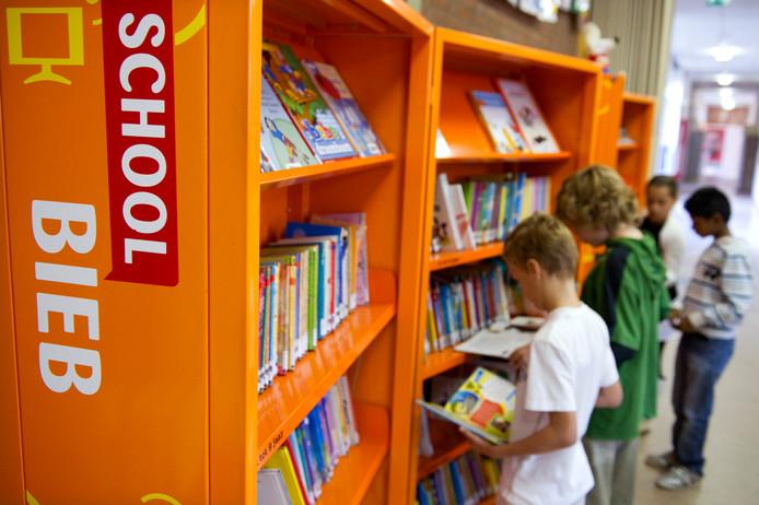 Kinderen uit groep 6 snuffelen tussen de boeken in een Bibliotheek op School.