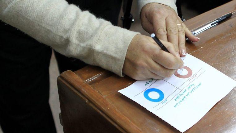 Een vrouw stemt bij de stembus tijdens de stemming voor de nieuwe conceptgrondwet. Beeld null